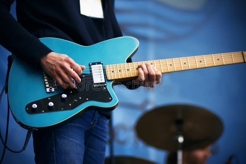 Музыкант утеса играет на гитаре голубой 6-строки электрической стоковое изображение rf