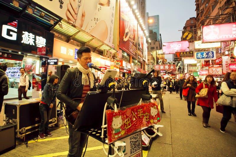 Музыкант утеса поет песню во время представления улицы в шумном городе стоковые фото