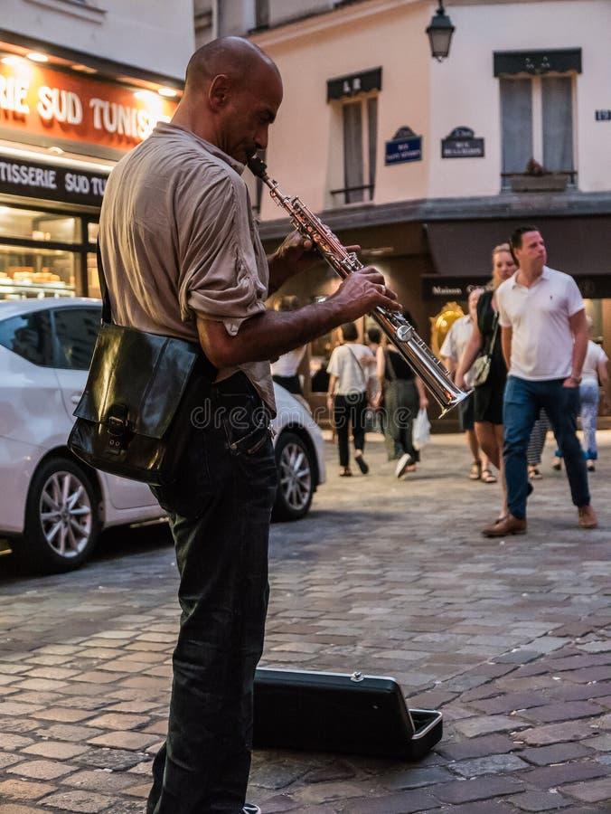 Музыкант улицы играет саксофон сопрано на тротуаре Парижа стоковые изображения