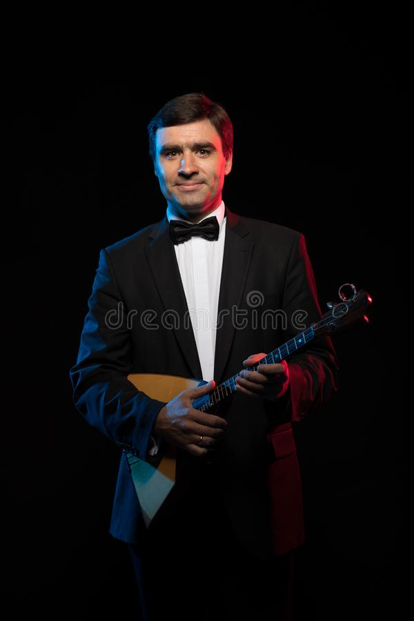 Музыкант художника, темн-с волосами человек в черном костюме и бабочка, игры балалайка стоковое изображение