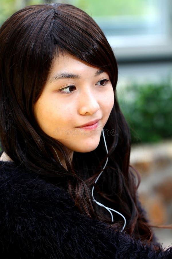 Музыка азиатской женщины слушая стоковая фотография