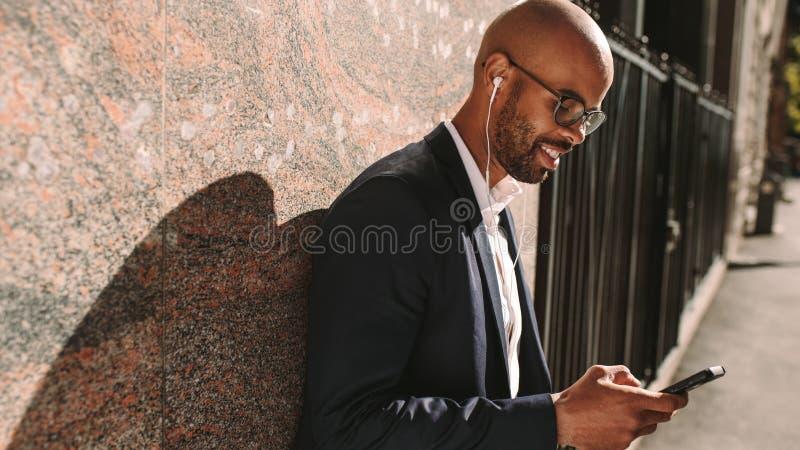 Музыка бизнесмена слушая с телефоном outdoors стоковая фотография