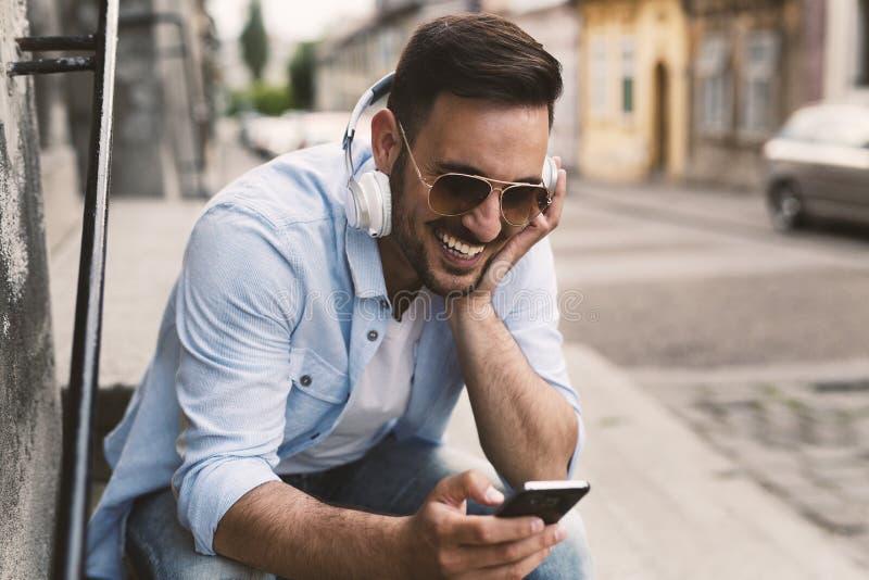 Музыка вскользь человека смеясь над и слушая стоковое фото
