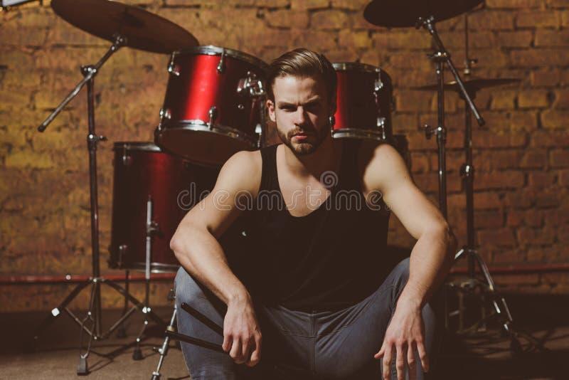 Музыка в воздухе Наслаждаться инструментальной музыкой Красивый человек сидит на этапе на ударном инструменте Барабанщик человека стоковое фото rf