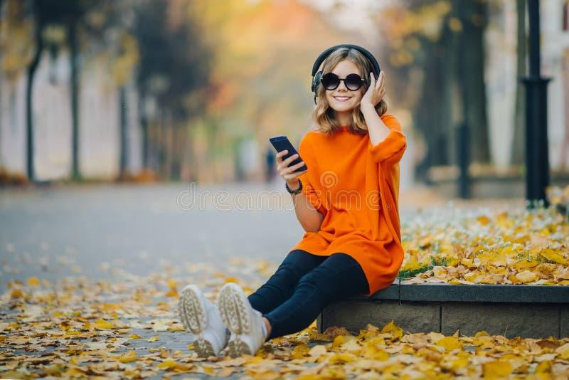 Музыка в наушниках, городской стиль милой маленькой девочки слушая, сидеть стильного хипстера предназначенный для подростков на т стоковое изображение rf