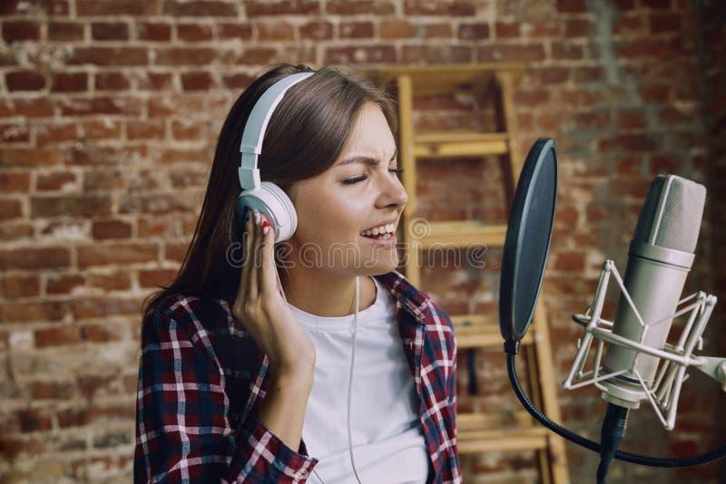 Музыка женщины записывая, передающ и поющ дома стоковая фотография rf