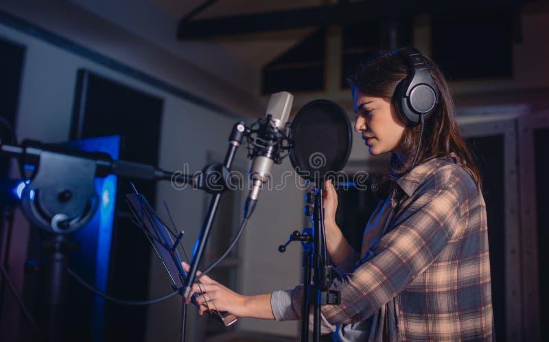 Музыка записи женщины в студии стоковые фотографии rf