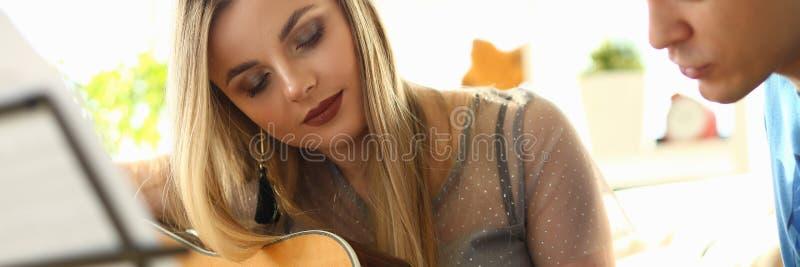 Музыка играя любовников урока соединяет на живущей комнате стоковые фото
