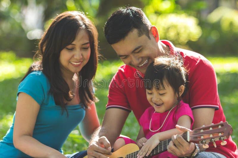 Музыка игры семьи в парке стоковые изображения