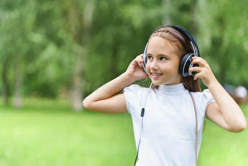 Музыка кавказской девушки детенышей усмехаясь слушая с профессиональными наушниками DJ и потехой получать стоковые изображения