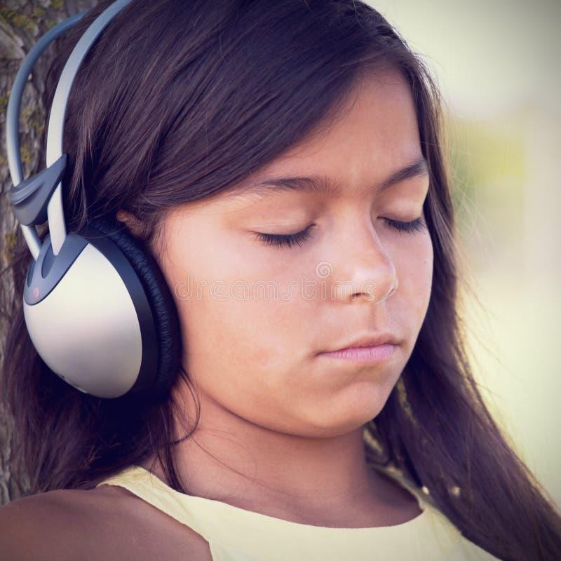Музыка маленького ребенка слушая стоковая фотография