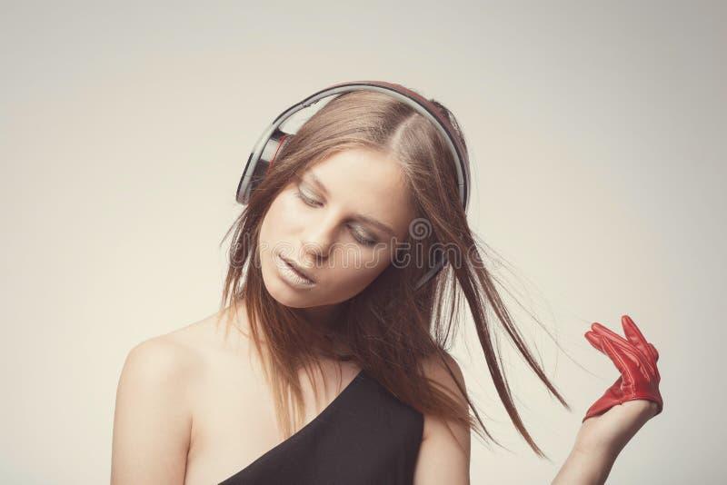 Музыка милой девушки моды слушая с наушниками, нося красными перчатками, близкими глазами и принять удовольствие с песней стоковые фото