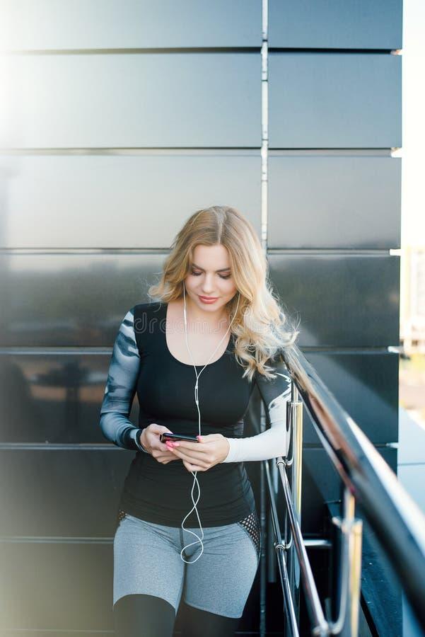 Музыка молодого привлекательного фитнеса модельная слушая на умном телефоне ch стоковая фотография rf