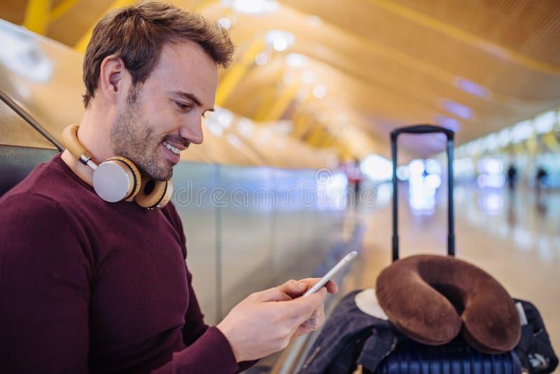 Музыка молодого человека ждать слушая и мобильный телефон использования на стоковая фотография