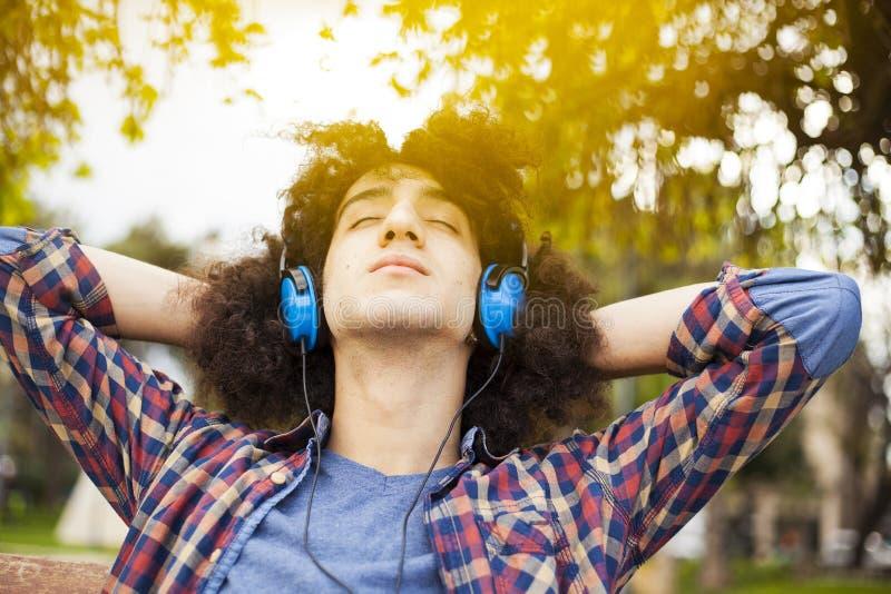 Музыка молодого человека слушая с наушниками стоковые фотографии rf