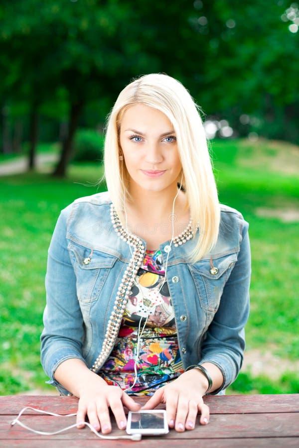 Музыка молодой белокурой девушки слушая стоковое фото