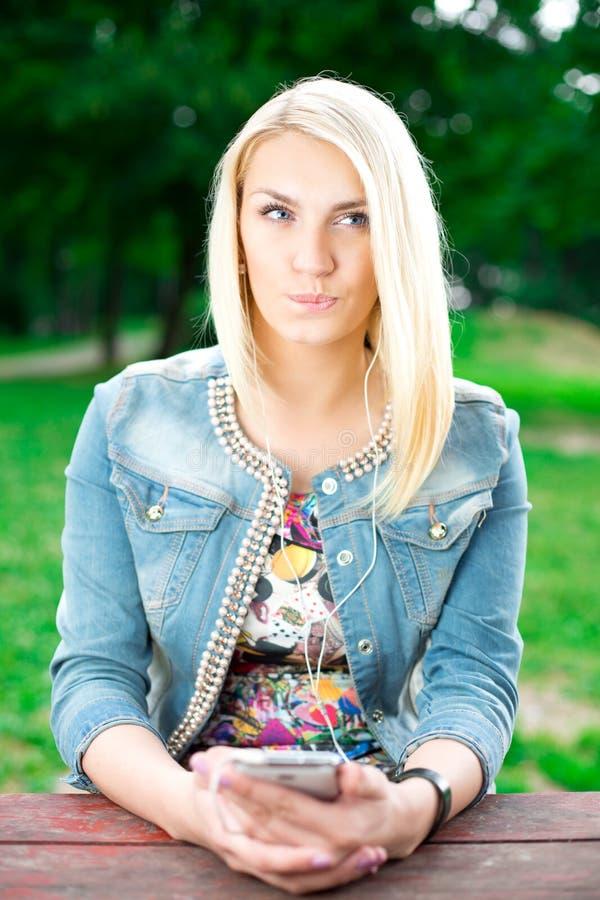 Музыка молодой белокурой девушки слушая стоковые фото