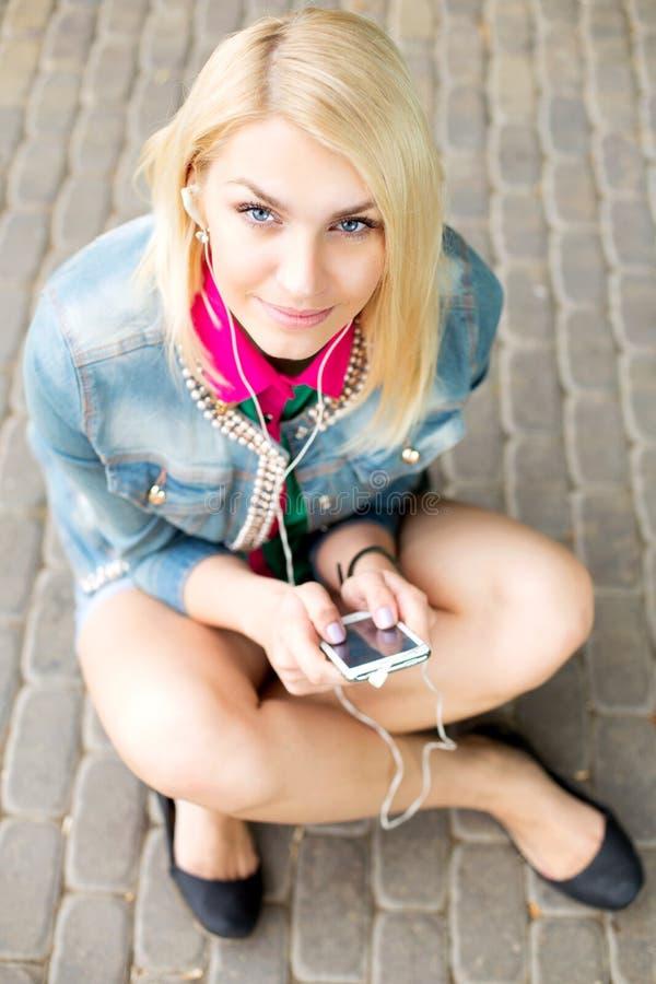 Музыка молодой белокурой девушки слушая стоковая фотография
