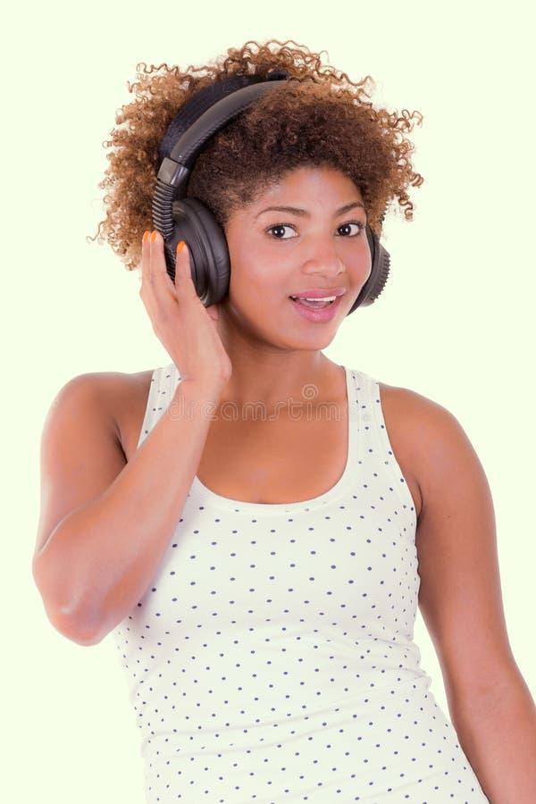 Музыка молодой чернокожей женщины слушая стоковое изображение rf