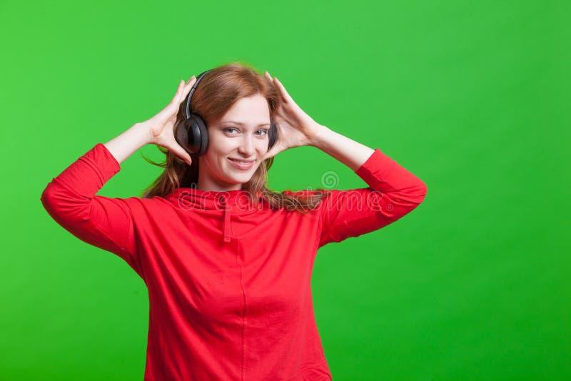 Музыка на наушниках, зеленая предпосылка женщины слушая стоковые изображения
