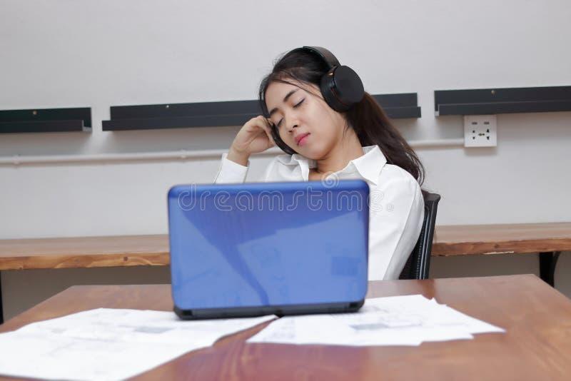 Музыка расслабленной молодой азиатской бизнес-леди слушая с глазами закрыла в рабочем месте стоковая фотография