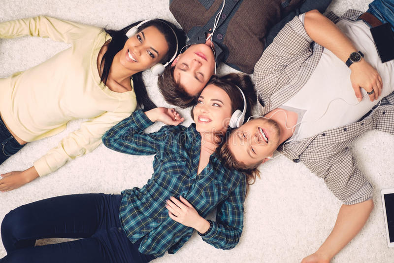 Музыка счастливых multiracial друзей слушая стоковые фотографии rf