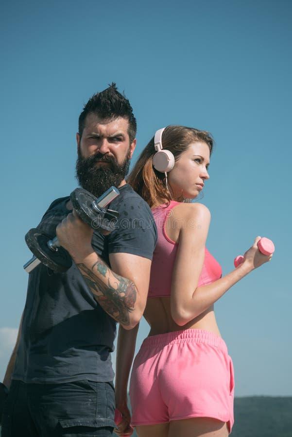 Музыка фитнеса оборудование штанги подниматься гантели r бородатые человек и женщина с подходящим животом r стоковые фотографии rf