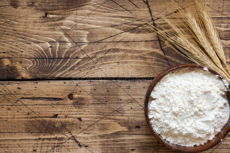 Мука в деревянных ушах шара и пшеницы на деревянной предпосылке скопируйте космос стоковая фотография