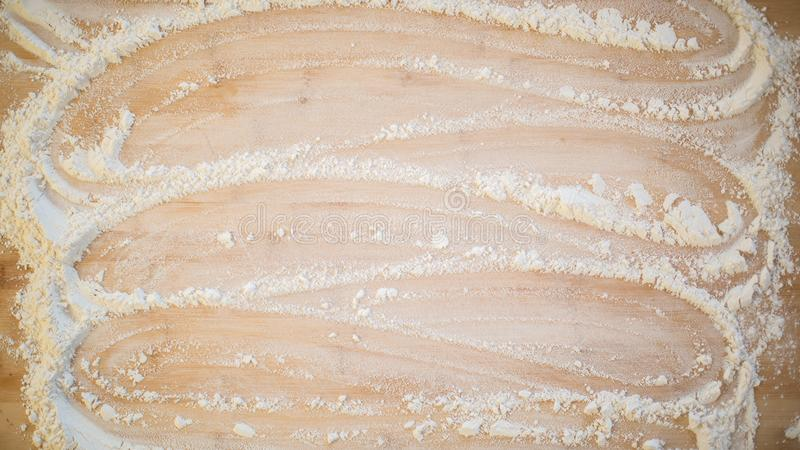 Мука приглаживаемая через деревянную разделочную доску стоковое фото