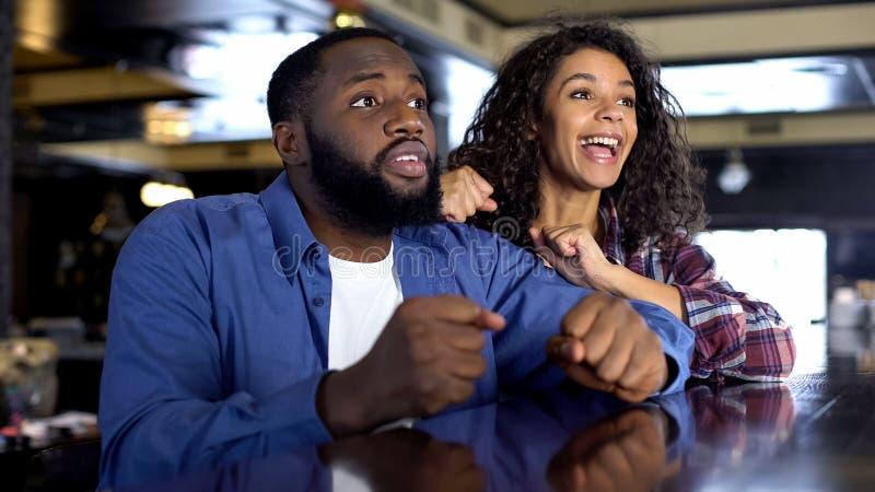 Мульти-расовые пары укореняя для игры национальной команды наблюдая, развлечений стоковое изображение