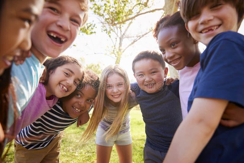 Мульти-этническая группа в составе школьники смеясь над и обнимая стоковое фото