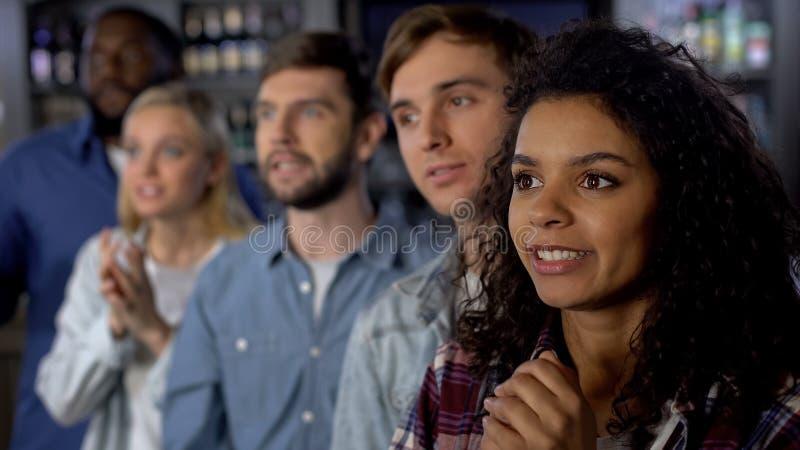Мульти-этническая девушка с друзьями укореняя для национальной команды, аудитория события стоковое изображение rf