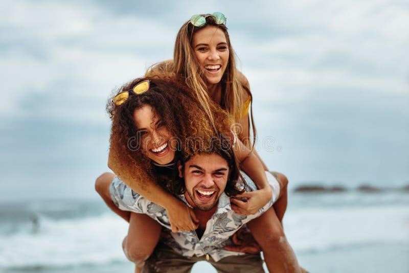 Мульти-этнические друзья наслаждаясь летними отпусками на пляже стоковое фото