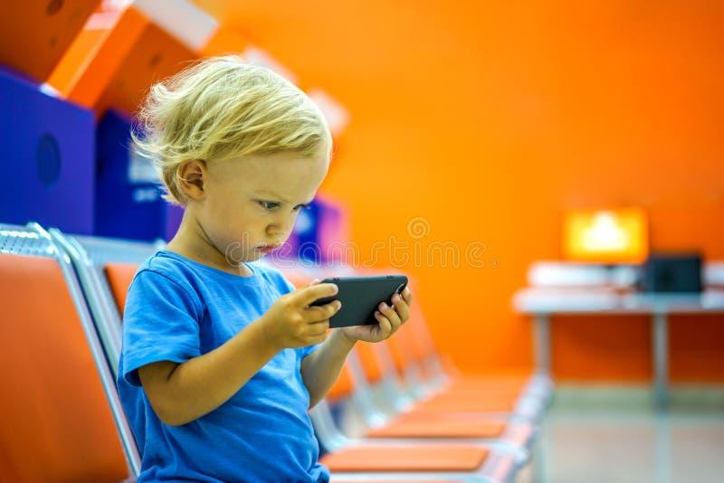 Мультфильмы милого мальчика наблюдая на смартфоне в зале ожидания стоковые изображения