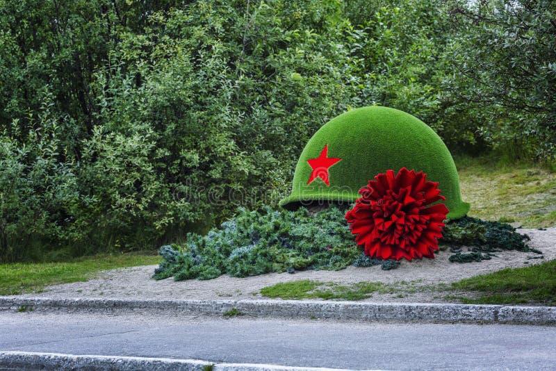 Мурманск, Россия, 08 29 2017: Памятник мертвым солдатам в форме шлема и красной гвоздики стоковая фотография