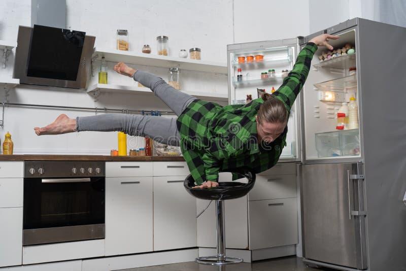 Мускулярный мужчина балансирует на одной руке на кухне Понятие здорового образа жизни и органической пищи стоковая фотография