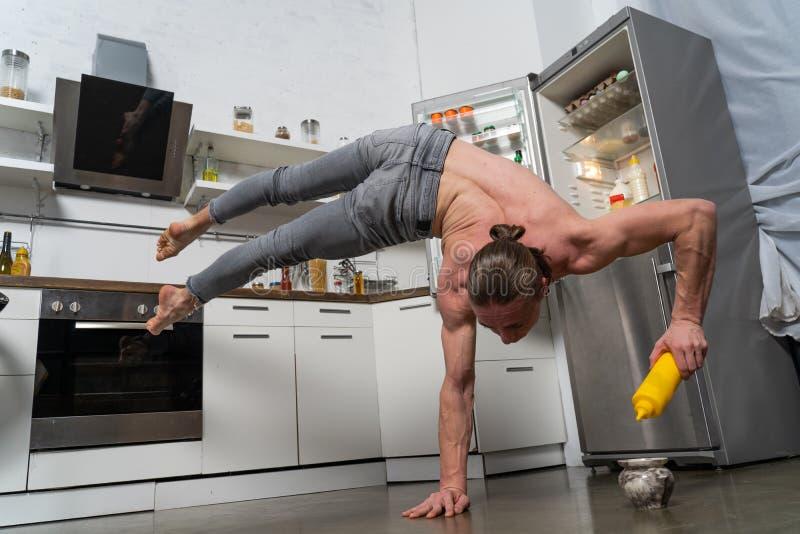 Мускулярный мужчина стоит на одной руке на кухне с бутылкой сума Понятие здорового образа жизни и органической пищи стоковое изображение rf