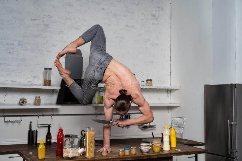 Мускуляр стоит на одной руке на кухне и держит нож Понятие здорового образа жизни и органической пищи стоковое изображение