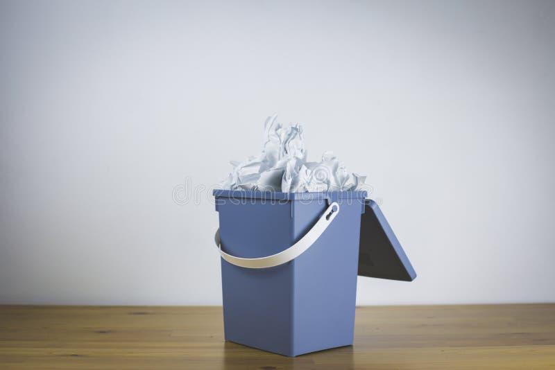 Мусорное ведро с крышкой совершенно заполненной со скомканной бумагой стоковые фотографии rf