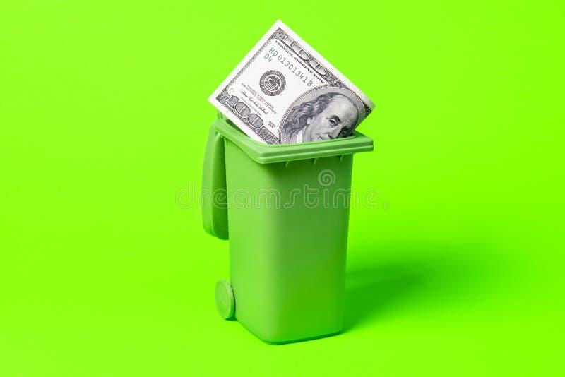 Мусорный бак денег изолированный на зеленой предпосылке стоковая фотография
