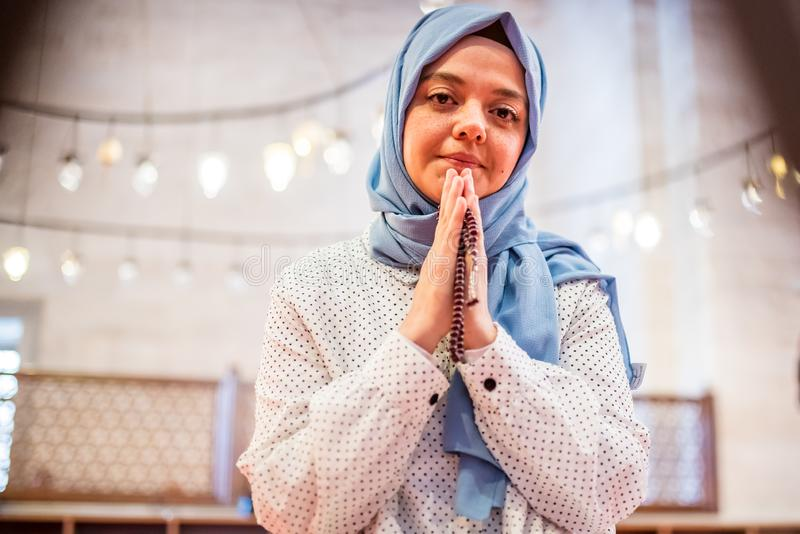 Мусульманская женщина в головном платке и hijab молит стоковые фотографии rf