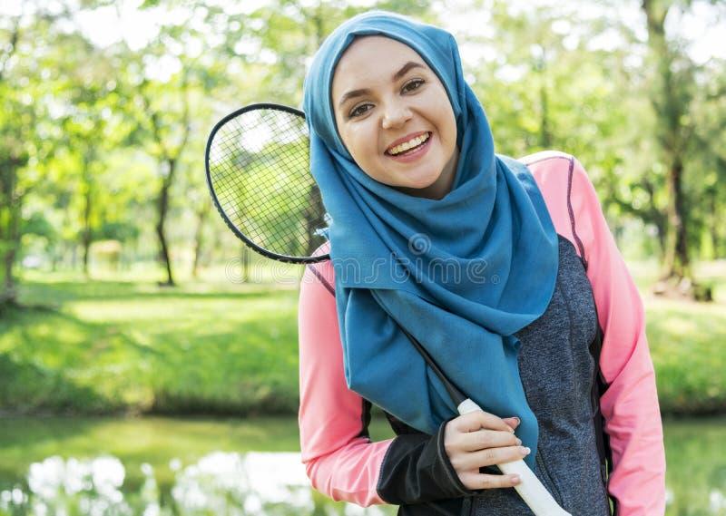 Мусульманская женщина играя бадминтон outdoors стоковые изображения rf