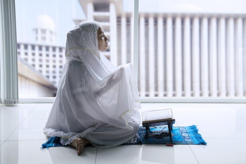 Мусульманская женщина молит к Аллаху дома стоковая фотография rf