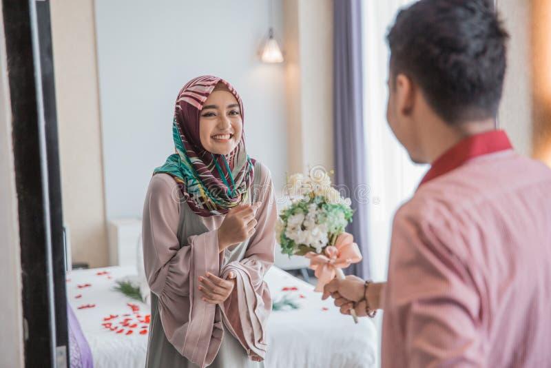 Мусульманская женщина получая цветок от ее супруга стоковые изображения