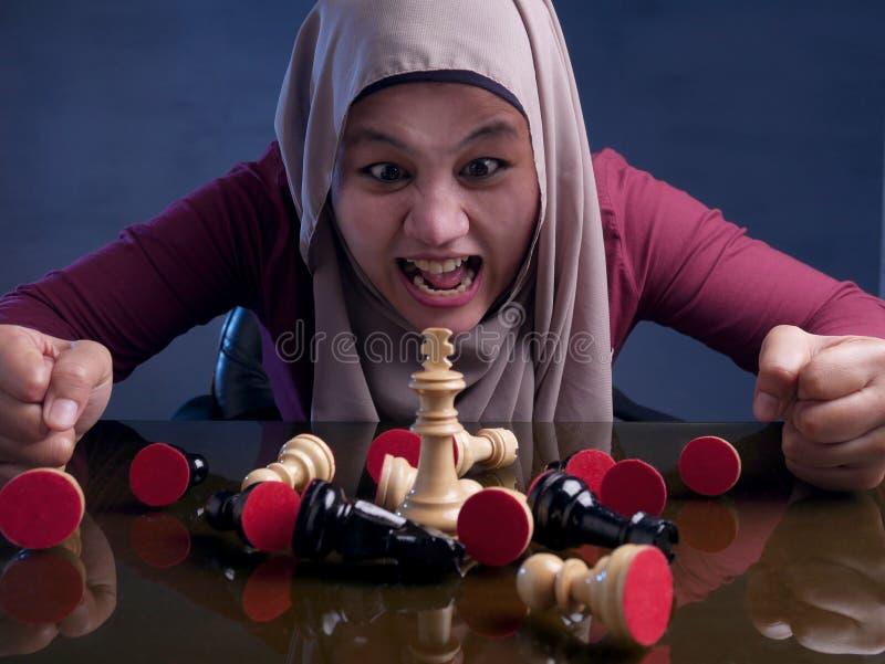 Мусульманская женщина сердится при игре шахмат стоковое фото rf