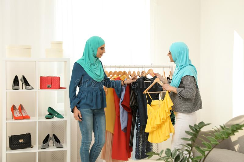 Мусульманская женщина с ее другом выбирая одежды стоковые фотографии rf