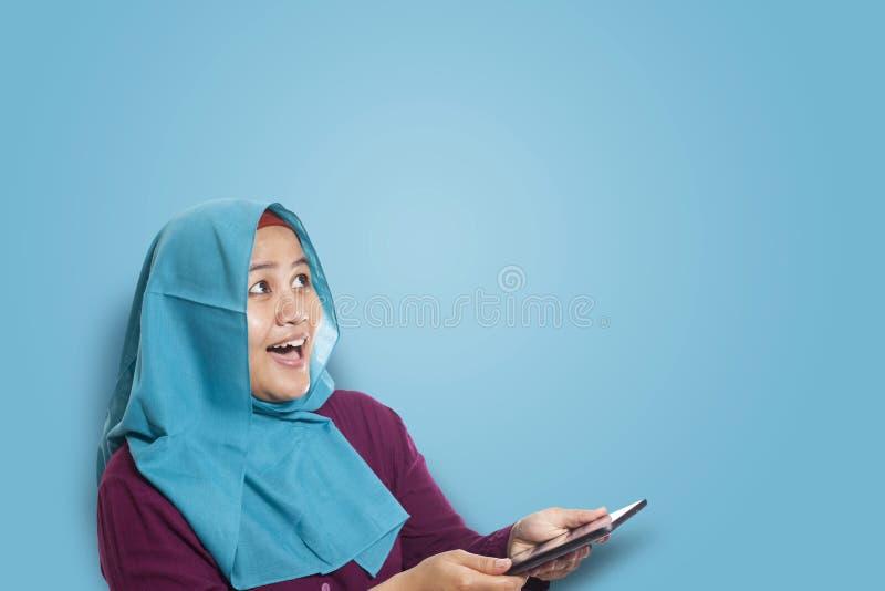 Мусульманская женщина удивленная увидеть что-то над при использовании телефона стоковая фотография rf