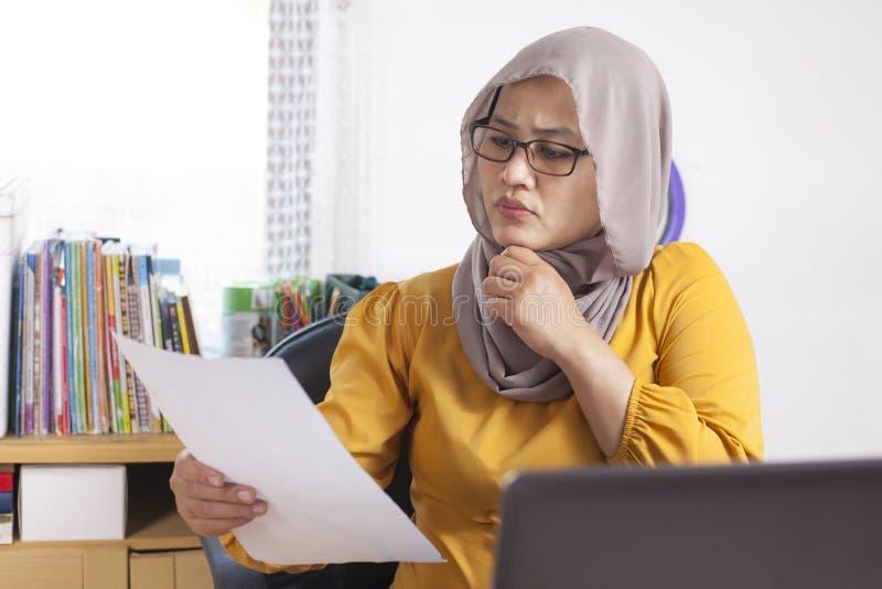 Мусульманская коммерсантка серьезно работая стоковые фотографии rf