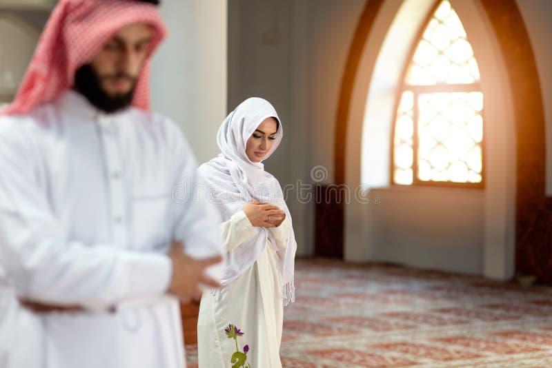 Мусульманские моля человек и женщина в мечети стоковое фото rf