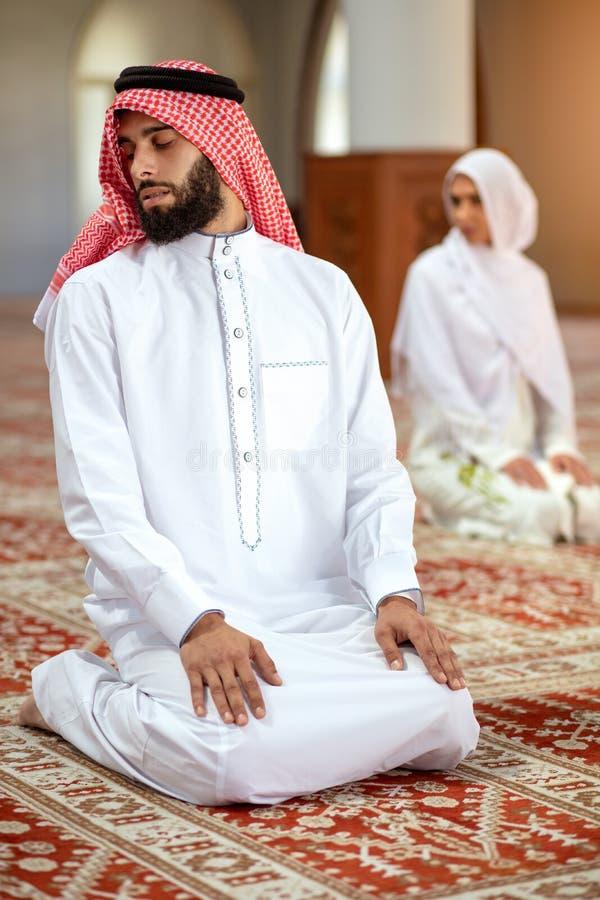 Мусульманские моля человек и женщина в мечети стоковое фото